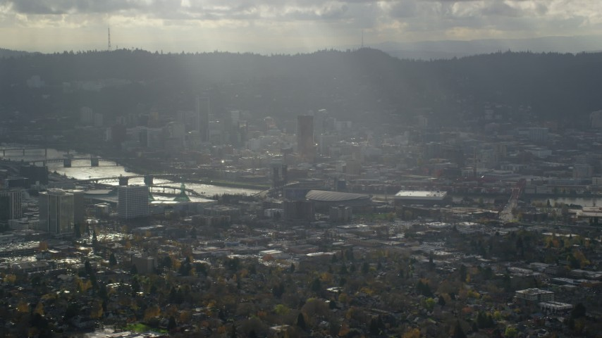 6K stock footage aerial video of godrays shining down on Moda Center, the Willamette River and Downtown Portland, Oregon Aerial Stock Footage | AX154_224