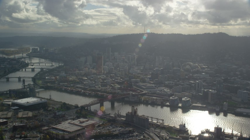 6K stock footage aerial video flying by the Willamette River and Downtown Portland, Oregon with godrays shining down Aerial Stock Footage | AX154_227