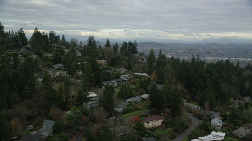 6K stock footage aerial video flying by hillside homes to reveal condo high-rises by the Willamette River in South Waterfront, Portland, Oregon Aerial Stock Footage   AX155_018
