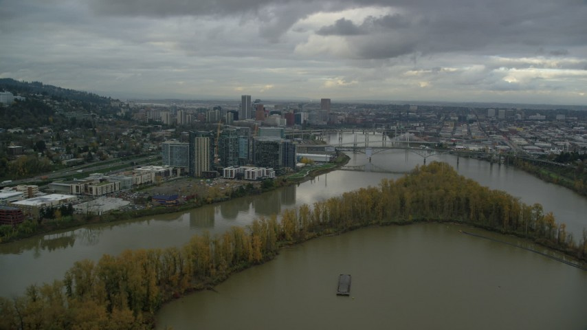 6K stock footage aerial video flying over Willamette River and Ross Island to approach South Waterfront and Downtown Portland, Oregon Aerial Stock Footage | AX155_026