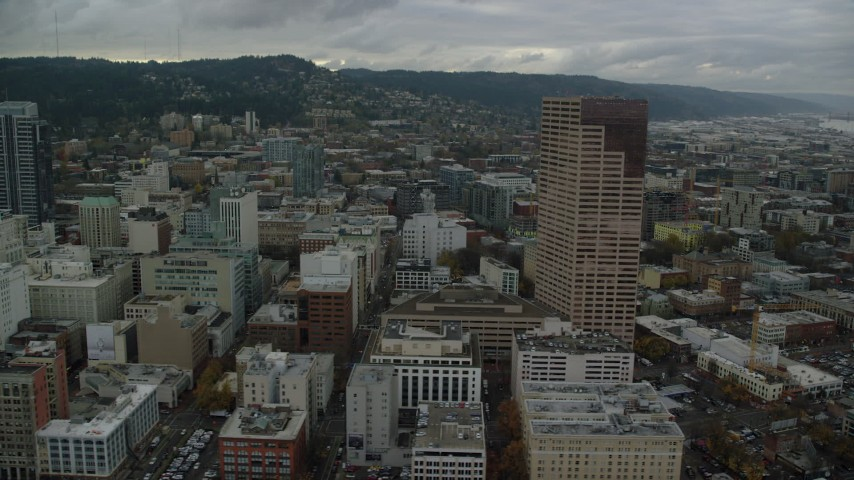 6K stock footage aerial video flying by US Bancorp Tower, downtown buildings and streets in Downtown Portland, Oregon Aerial Stock Footage | AX155_031