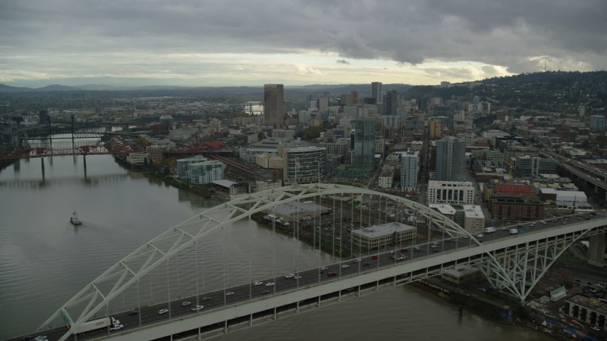 6K stock footage aerial video flying by the Fremont Bridge and focus on skyscrapers in Downtown Portland, Oregon Aerial Stock Footage | AX155_036