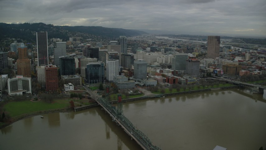 6K stock footage aerial video passing by skyscrapers, downtown buildings, and city park near the river in Downtown Portland, Oregon Aerial Stock Footage | AX155_051