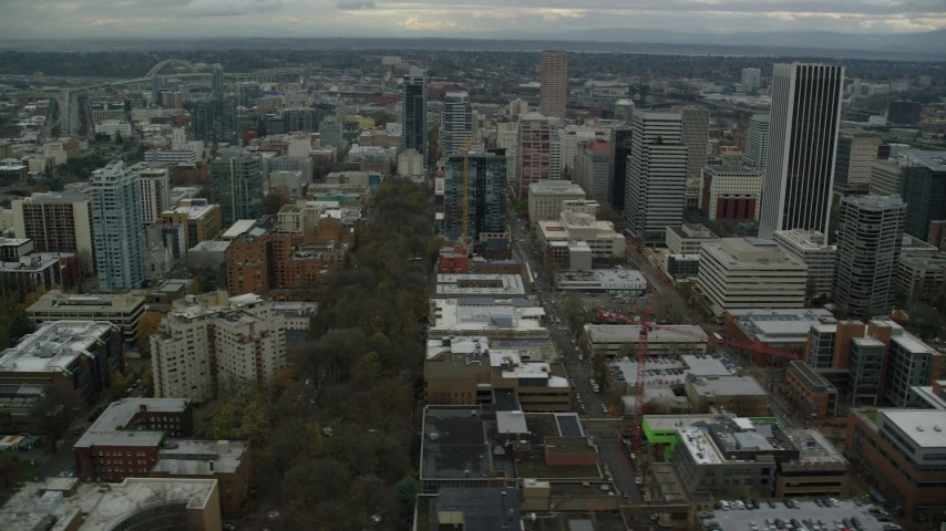 6K stock footage aerial video flying by South Park Blocks, city streets and skyscrapers near the river in Downtown Portland, Oregon Aerial Stock Footage | AX155_060