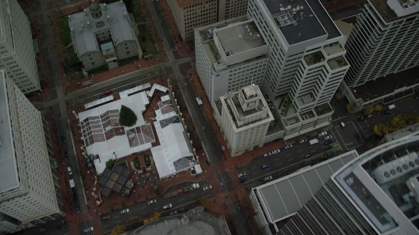 6K stock footage aerial video of a bird's eye view of city streets, Pioneer Courthouse Square, skyscrapers, and reveal Salmon Street Springs fountain in Downtown Portland, Oregon Aerial Stock Footage | AX155_076