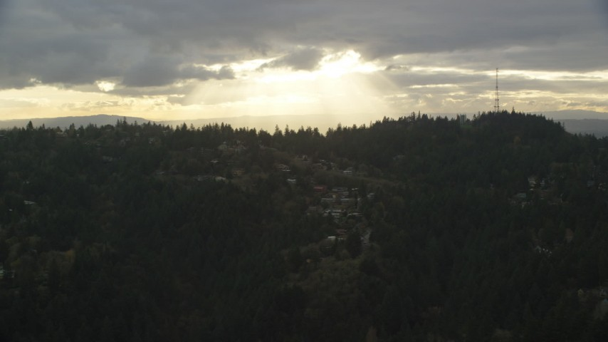 6K stock footage aerial video of homes and trees on a hillside, with godrays through clouds in the background, Southwest Portland, Oregon Aerial Stock Footage | AX155_092