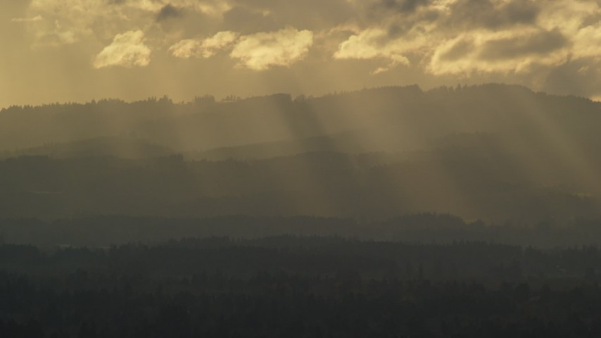 6K stock footage aerial video of godrays shining down on mountains near Beaverton, Oregon at sunset Aerial Stock Footage | AX155_124