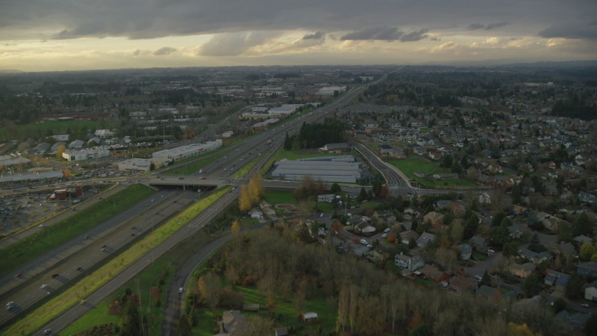 6K aerial video flying over suburban homes to approach apartment buildings and Highway 26 in Beaverton, Oregon, twilight Aerial Stock Footage | AX155_126