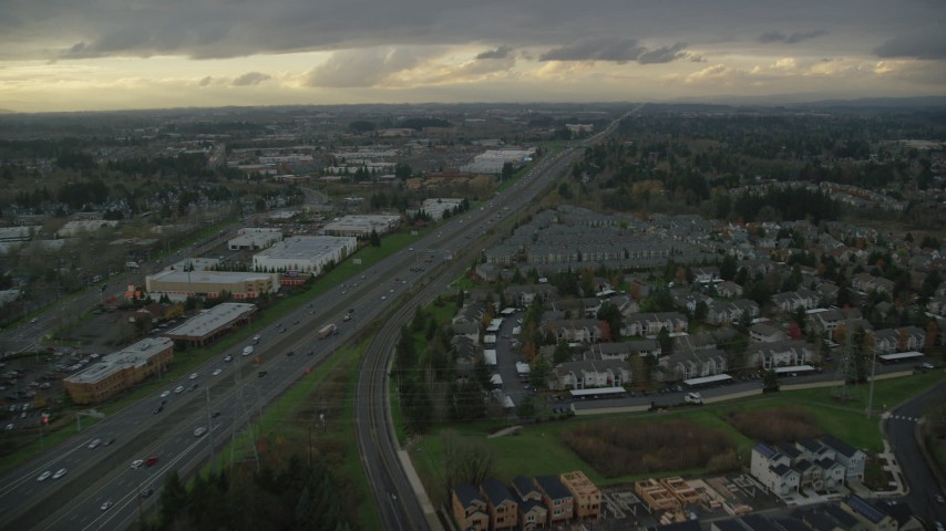 6K stock footage aerial video flying over fly over apartment buildings and follow Highway 26 by Tanasbourne Town Center in Hillsboro, Oregon, twilight Aerial Stock Footage | AX155_127