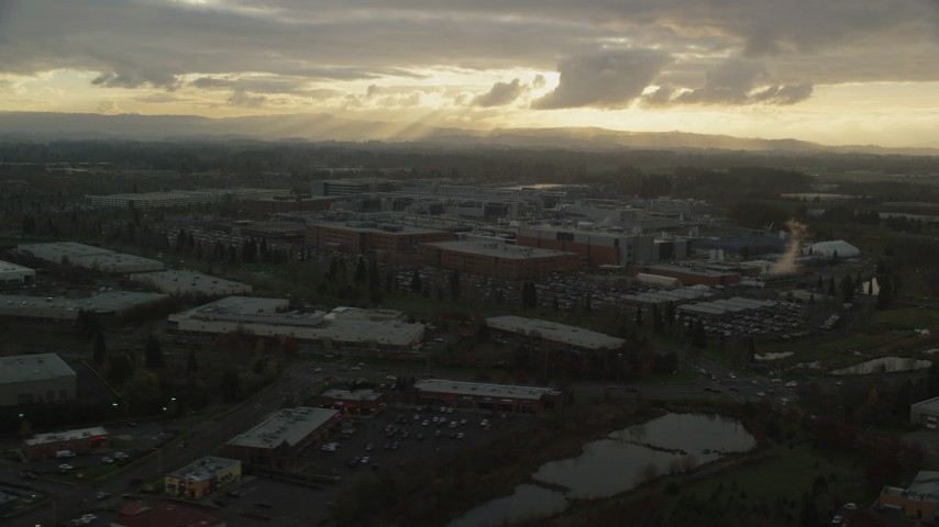 6K stock footage aerial video passing Intel Ronler Acres with godrays in the background, in Hillsboro, Oregon, sunset Aerial Stock Footage | AX155_131