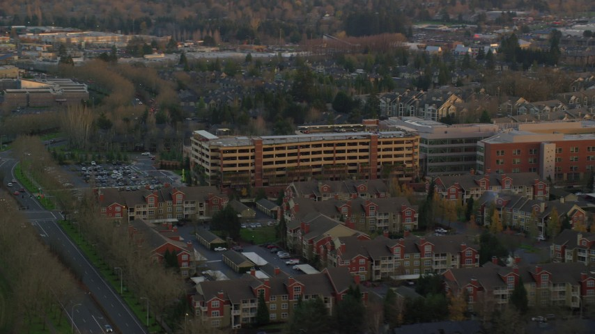 6K stock footage aerial video flying by a large parking garage and the Kaiser Permanente Medical Offices at twilight in Hillsboro, Oregon Aerial Stock Footage | AX155_134