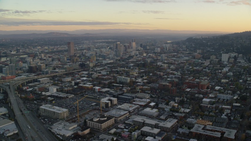 6K stock footage aerial video flying over Northwest Portland at twilight to approach I-405 and Downtown Portland Aerial Stock Footage | AX155_143