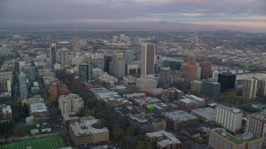 6K stock footage aerial video orbiting skyscrapers and city streets near the Willamette River at twilight in Downtown Portland, Oregon Aerial Stock Footage | AX155_149