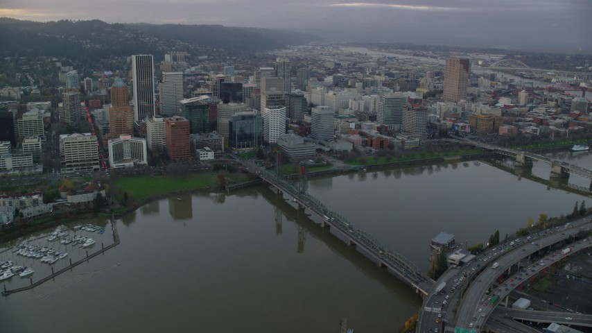6K stock footage aerial video of Downtown Portland skyscrapers and city park seen across the Willamette River at twilight Aerial Stock Footage | AX155_153