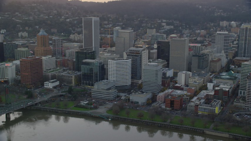 6K stock footage aerial video of Downtown Portland skyscrapers and city park beside the Willamette River at twilight Aerial Stock Footage | AX155_154