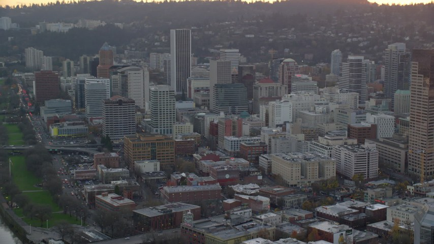6K stock footage aerial video flying by skyscrapers and high-rises in Downtown Portland, Oregon, twilight Aerial Stock Footage | AX155_156