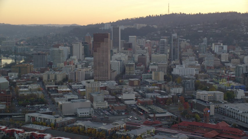 6K aerial video flying by skyscrapers and high-rises at twilight in Downtown Portland, Oregon, reveal Union Station Aerial Stock Footage | AX155_157