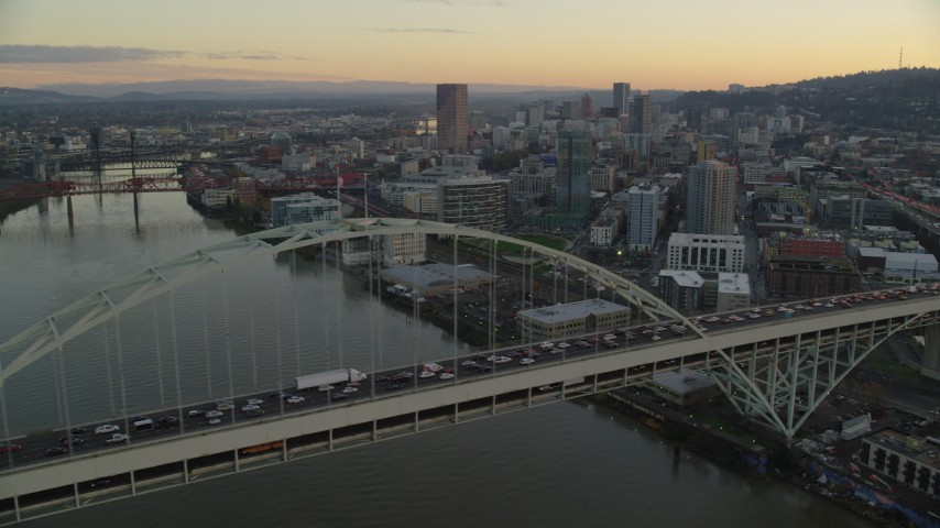 6K stock footage aerial video of heavy traffic crossing the Fremont Bridge at twilight, and Downtown Portland skyscrapers in the background Aerial Stock Footage | AX155_160