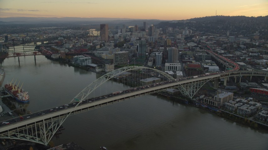 6K stock footage aerial video flying over heavy traffic on the Fremont Bridge at twilight, approach Downtown Portland, Oregon Aerial Stock Footage AX155_162 | Axiom Images
