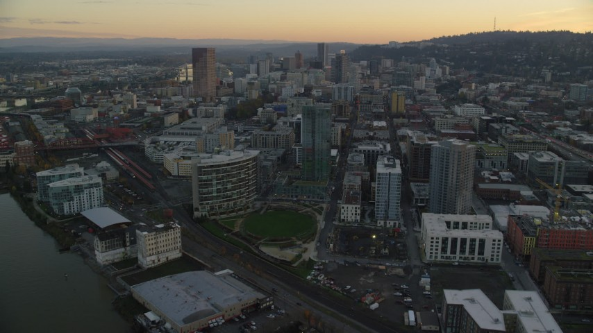 6K stock footage aerial video flying over The Fields Park and high-rise, and follow NW 11th Avenue through Downtown Portland, Oregon, twilight Aerial Stock Footage | AX155_163