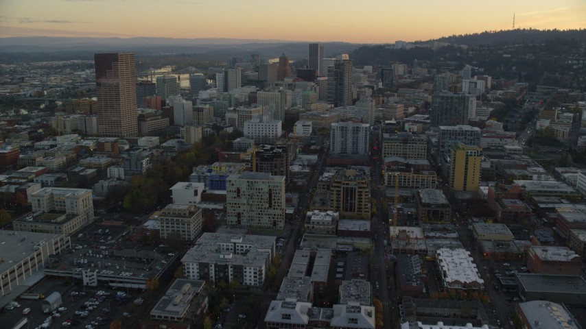 6K stock footage aerial video following NW 10th Avenue through Downtown Portland, Oregon, at twilight to approach Park Avenue West Tower Aerial Stock Footage | AX155_164