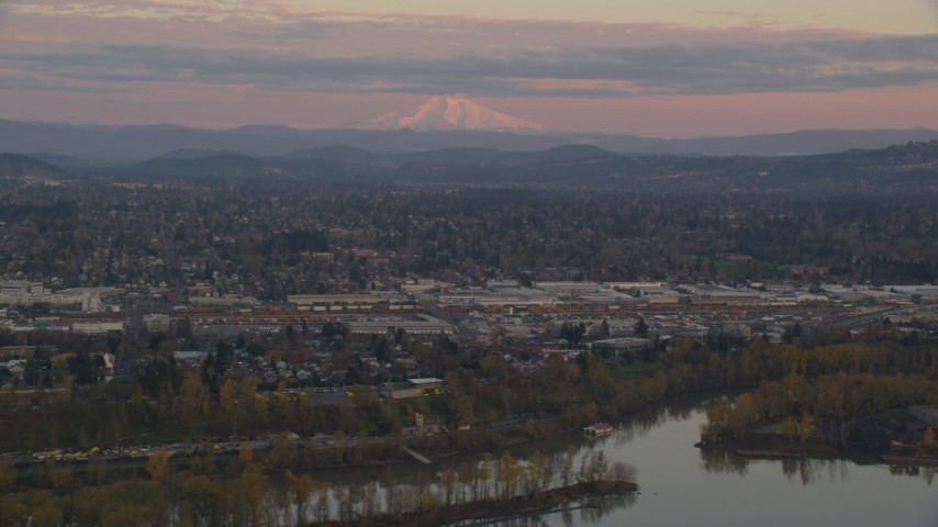 6K stock footage aerial video of Mount Hood in the far distance at twilight, seen from a train yard in Southeast Portland, Oregon Aerial Stock Footage | AX155_169