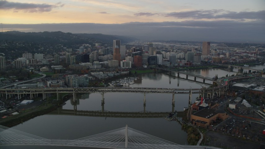 6K aerial video following the Willamette River over bridges to approach Downtown Portland at twilight, Oregon Aerial Stock Footage | AX155_172