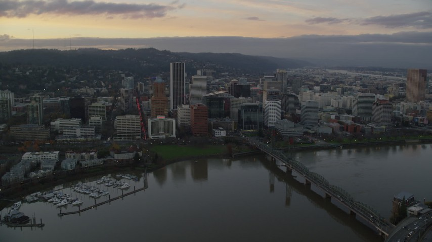 6K stock footage aerial video flying by the Hawthorne Bridge, waterfront park, and Downtown Portland at twilight in Oregon Aerial Stock Footage | AX155_173