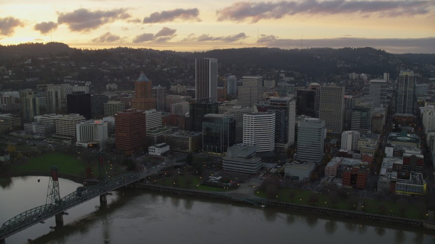 6K stock footage aerial video flying by the Hawthorne Bridge, the waterfront park and Downtown Portland at twilight in Oregon Aerial Stock Footage | AX155_174