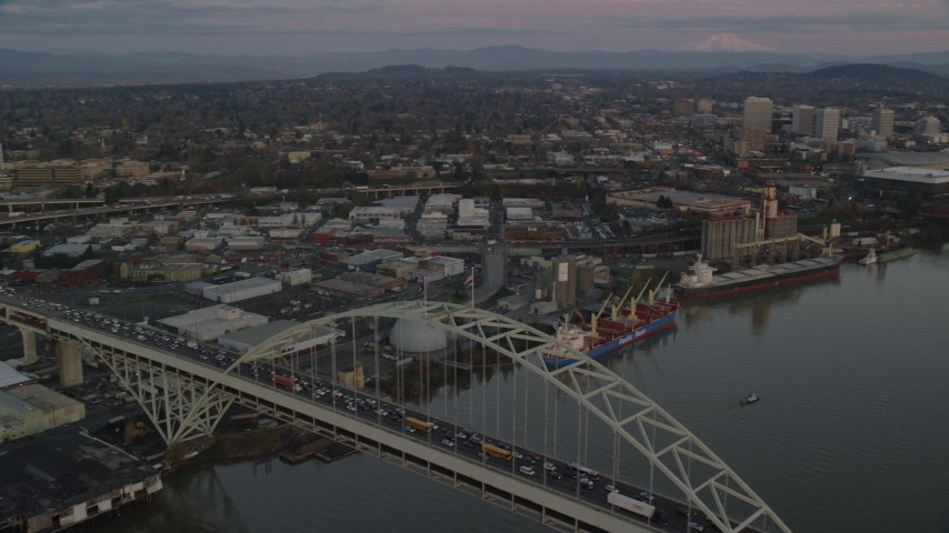 6K stock footage aerial video orbiting the Fremont Bridge with very heavy traffic at twilight, to reveal Downtown Portland, Oregon Aerial Stock Footage | AX155_183