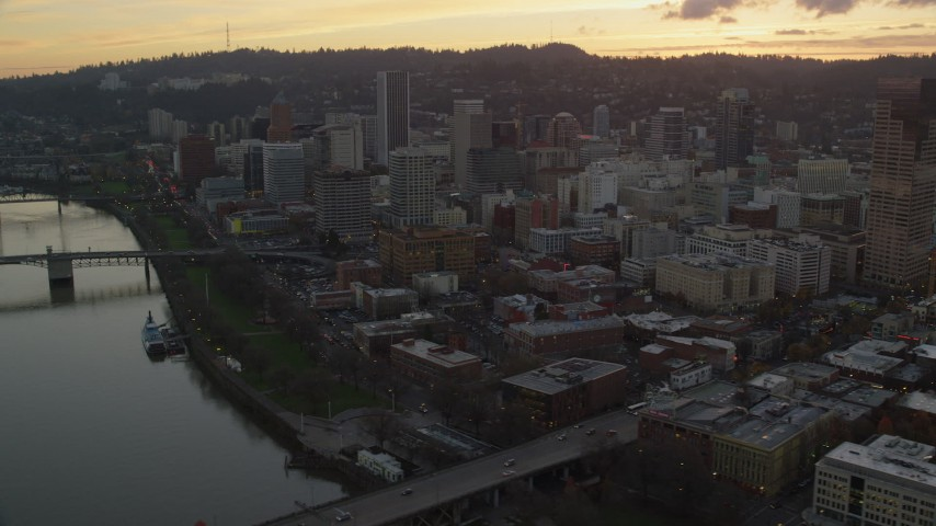 6K stock footage aerial video of Downtown Portland skyscrapers seen from the Morrison Bridge and the Willamette River at twilight in Oregon Aerial Stock Footage | AX155_187