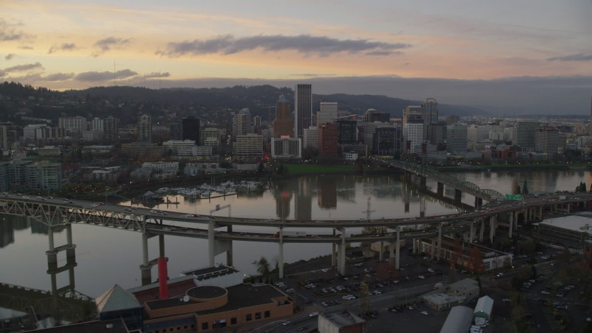 6K stock footage aerial video of Downtown Portland skyline seen while flying by Willamette River bridges at twilight, Oregon Aerial Stock Footage AX155_190 | Axiom Images
