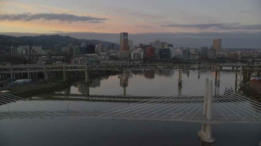 6K stock footage aerial video of Downtown Portland skyline and Marquam Bridge seen from Tilikum Crossing at twilight, Oregon Aerial Stock Footage | AX155_191
