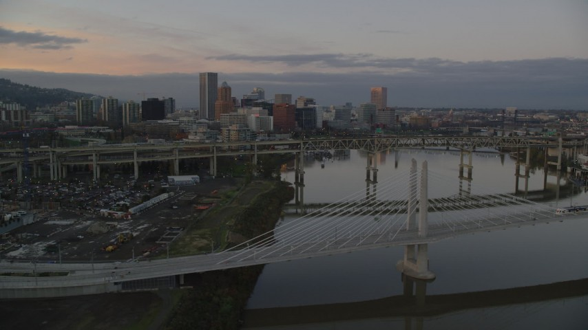 6K stock footage aerial video of Downtown Portland skyline and Marquam Bridge seen from Tilikum Crossing at twilight, and reveal an office building Aerial Stock Footage | AX155_192
