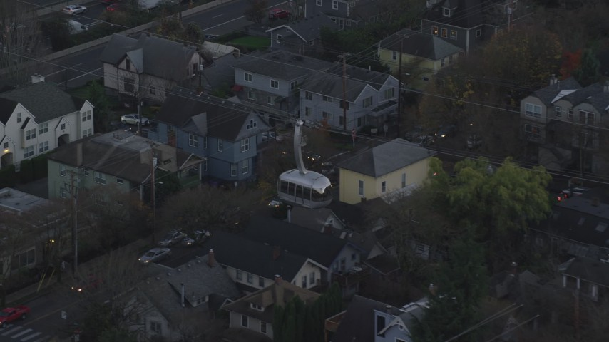 6K stock footage aerial video tracking a gondola over apartment buildings at twilight and reveal a second gondola, South Portland, Oregon Aerial Stock Footage | AX155_194