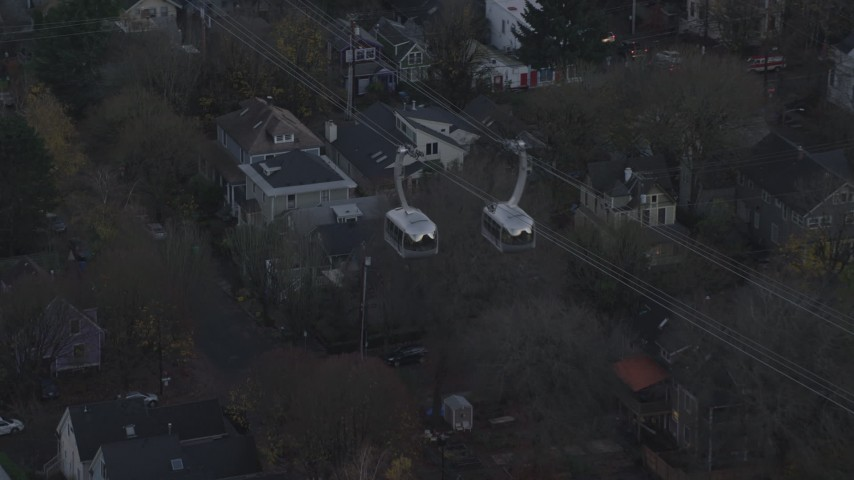 6K stock footage aerial video tracking a gondola over apartment buildings and busy streets at twilight, South Portland, Oregon Aerial Stock Footage | AX155_195