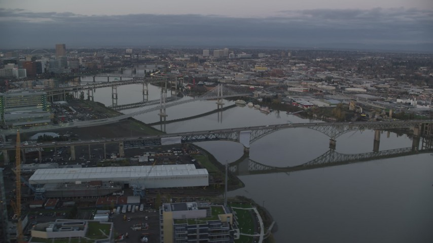 6K stock footage aerial video of Ross Island Bridge and Willamette River bridges at twilight, reveal Downtown Portland, Oregon Aerial Stock Footage | AX155_197