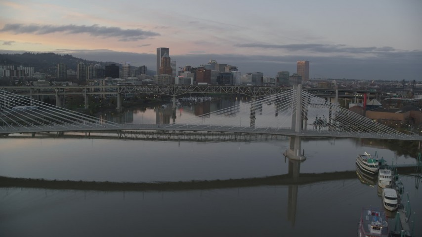 6K stock footage aerial video flying over Tilikum Crossing, approach Marquam Bridge and downtown skyline at twilight, Downtown Portland, Oregon Aerial Stock Footage | AX155_200