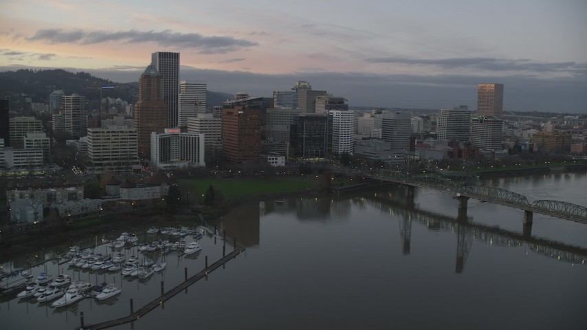 6K stock footage aerial video flying over Hawthorne Bridge, and pass the downtown skyline at twilight, Downtown Portland, Oregon Aerial Stock Footage | AX155_202