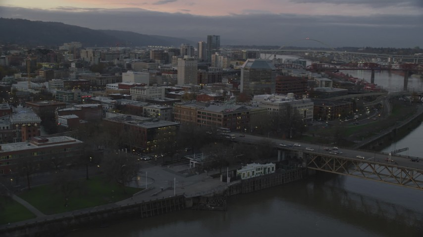 6K stock footage aerial video flying over Burnside Bridge, and pass the White Stag sign at twilight, Downtown Portland, Oregon Aerial Stock Footage | AX155_204