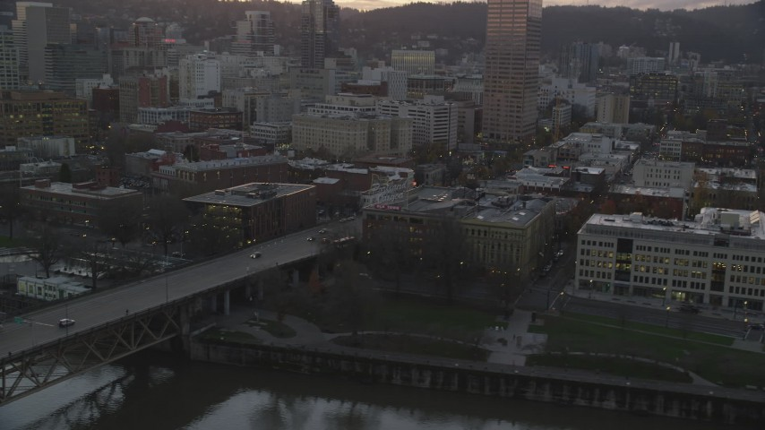 6K stock footage aerial video flying by the White Stag sign at twilight, with US Bancorp Tower behind it, Downtown Portland, Oregon Aerial Stock Footage   AX155_205