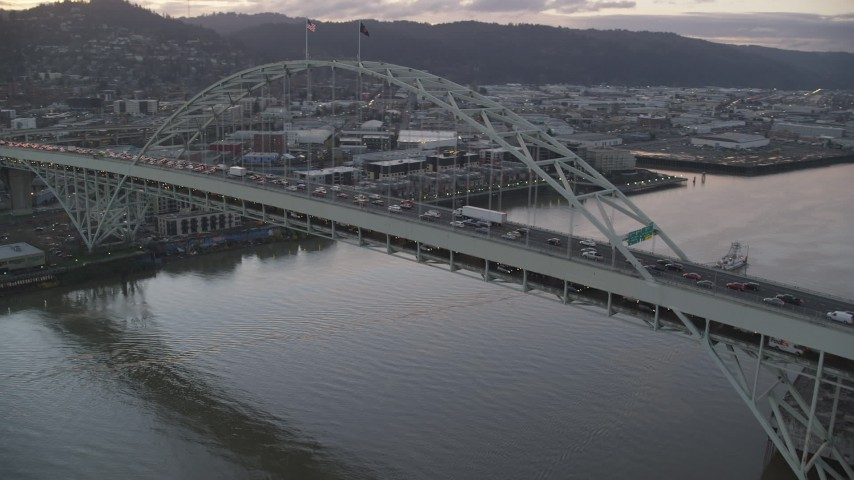 6K stock footage aerial video orbiting heavy rush-hour traffic on both decks of the Fremont Bridge, and reveal Downtown Portland, Oregon, twilight Aerial Stock Footage | AX155_209
