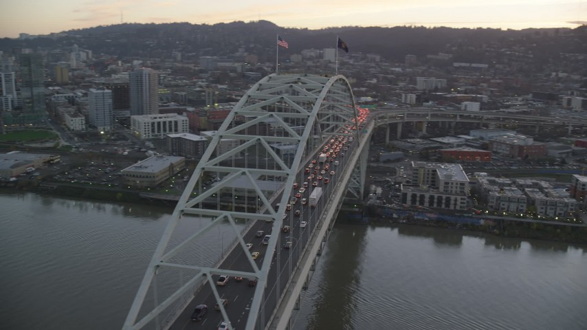 6K stock footage aerial video orbiting heavy traffic on both decks of the Fremont Bridge, and reveal Downtown Portland, Oregon, twilight Aerial Stock Footage | AX155_210