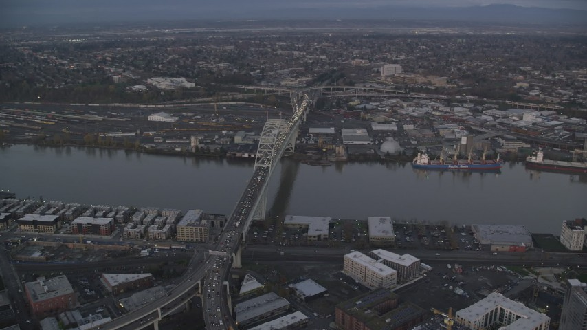 6K stock footage aerial video orbiting the Fremont Bridge with heavy traffic spanning Willamette River at twilight, Portland, Oregon Aerial Stock Footage | AX155_217