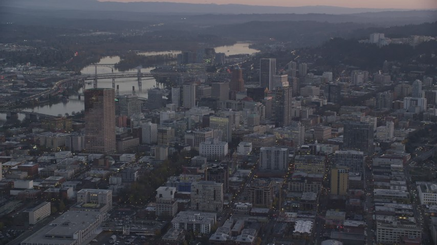 6K stock footage aerial video flying by Downtown Portland cityscape by the Willamette River at twilight, Oregon Aerial Stock Footage | AX155_219