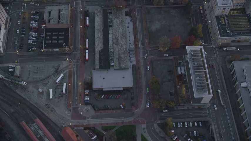 6K stock footage aerial video of a bird's eye view of bus station and downtown buildings between NW 5th and 6th Avenue at twilight, Downtown Portland, Oregon Aerial Stock Footage | AX155_221