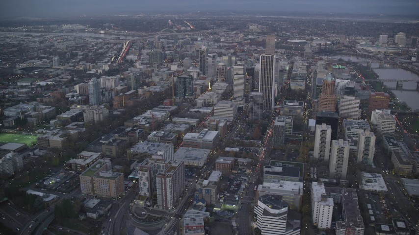 6K stock footage aerial video flying over streets toward Wells Fargo Center and tilt down at twilight, Downtown Portland, Oregon Aerial Stock Footage | AX155_228