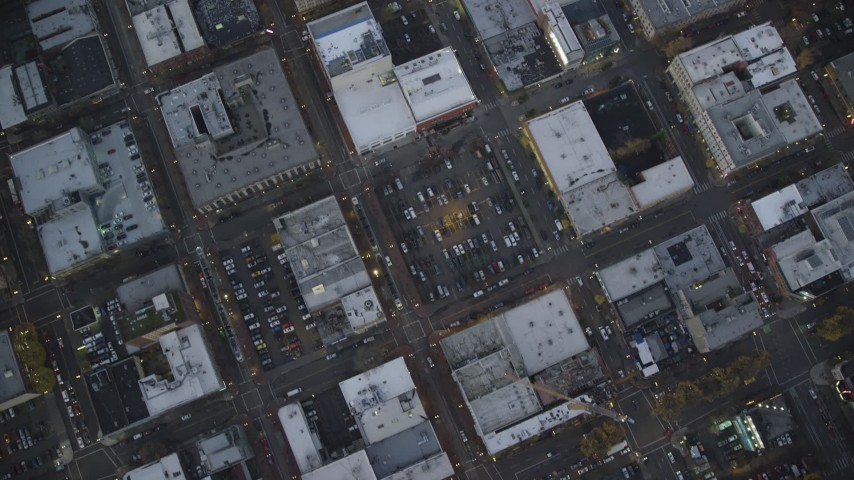 6K stock footage aerial video of a bird's eye view of buildings between NW 6th Avenue NW 5th Avenue at twilight, reveal Greyhound bus station, Downtown Portland, Oregon Aerial Stock Footage | AX155_234