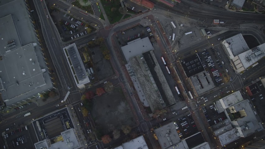 6K stock footage aerial video of a bird's eye view of city streets and Greyhound bus station, reveal Union Station at twilight, Downtown Portland, Oregon Aerial Stock Footage | AX155_235