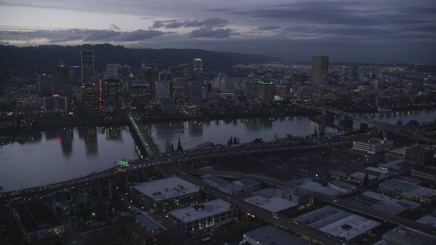 6K stock footage aerial video passing by skyscrapers and bridges over the Willamette River at twilight, Downtown Portland, Oregon Aerial Stock Footage | AX155_252